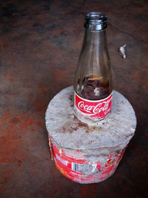 reusing -> holder for winding tool of tomato sauce can, concrete and cocacola glass